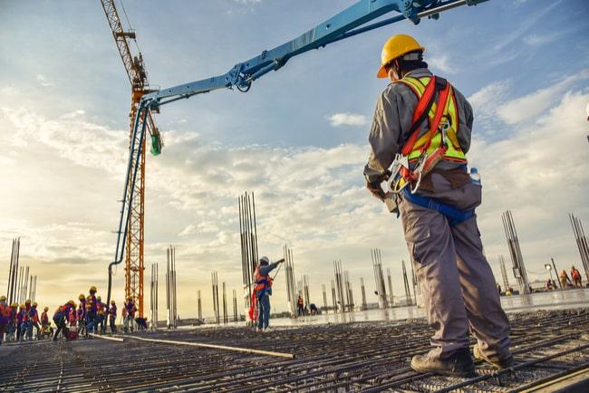 Byggarbetare står och tittar på lyftkran på byggarbetsplats