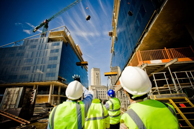Byggare tittar upp mot ett flerfamiljshus som byggs
