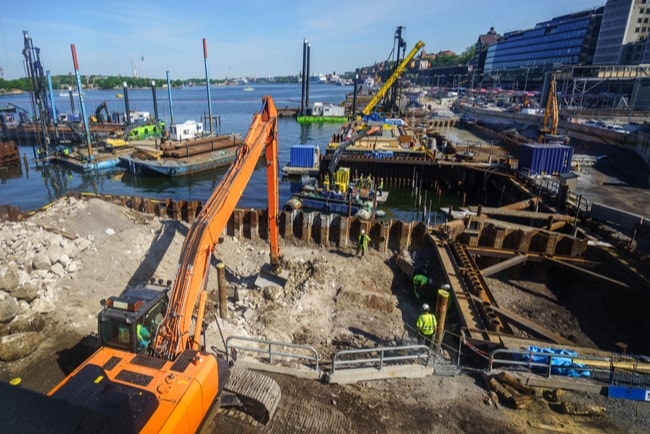 Grävskopa och byggarbetare på byggarbetsplats