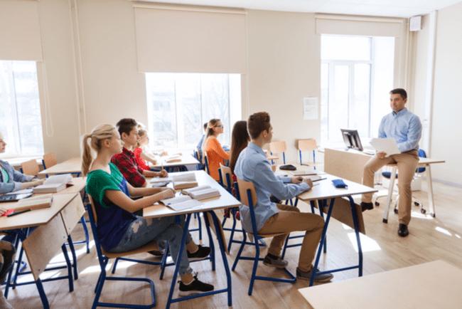 Klassrum sett från sidan med elever som sitter vid sina bänkar och lyssnar på sin manliga lärare som sitter på sitt skrivbord.