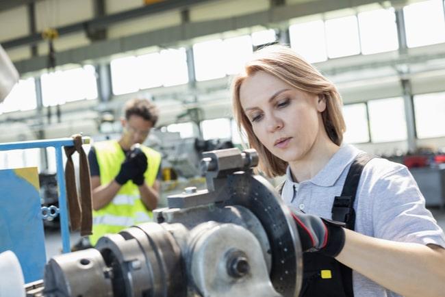 Kvinnlig arbetare på fabrik som ser mycket koncentrerad ut.