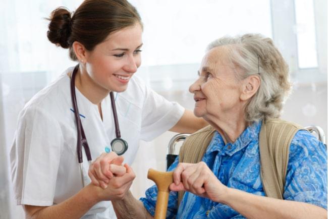 sjuksköterska håller äldre kvinna i handen