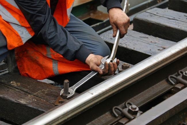 Järnvägsarbetare skruvar med skiftnycklar på järnväg