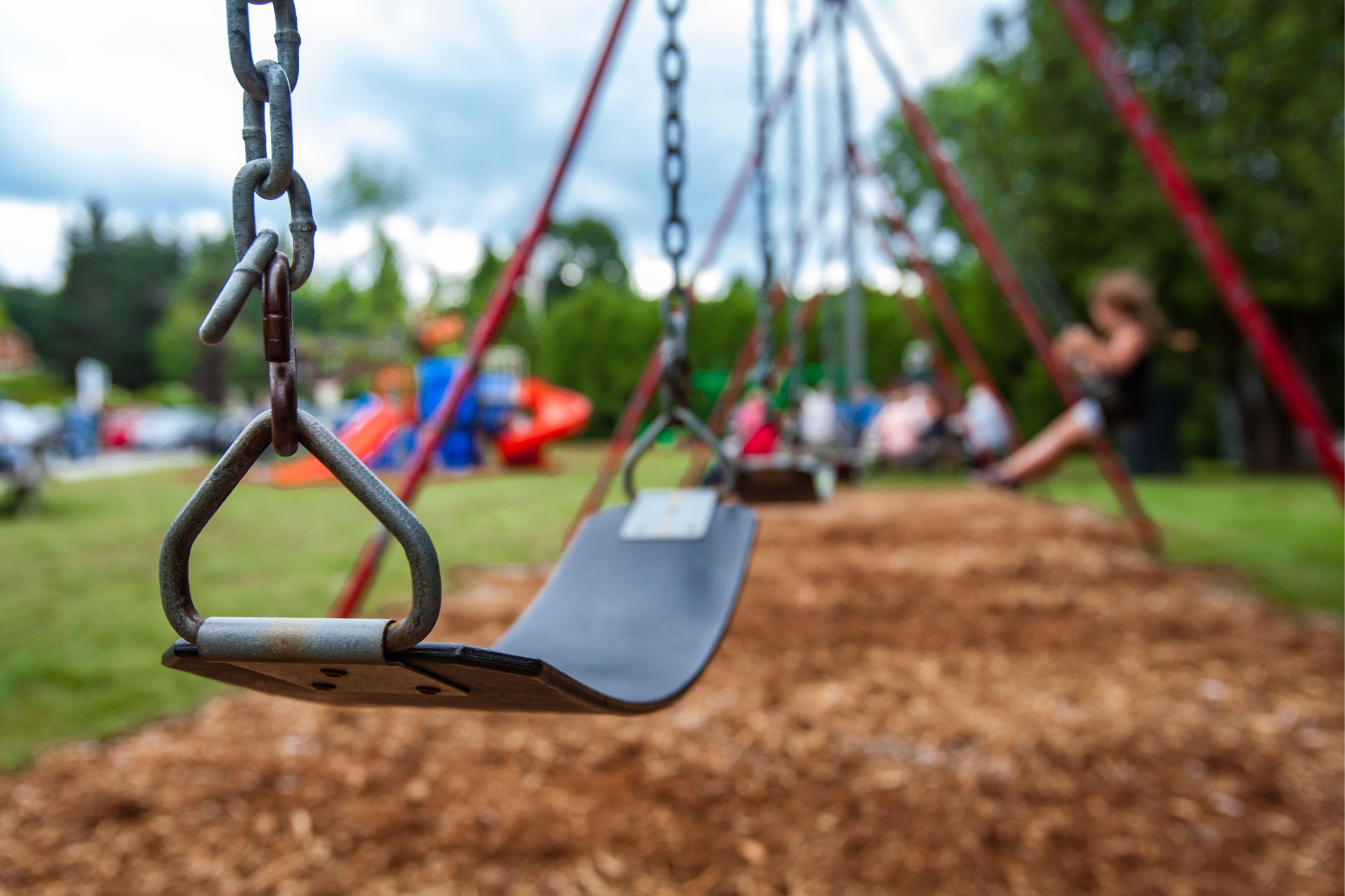 gunga i lekpark med lekande barn i bakgrunden