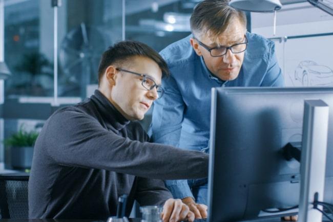 två män jobbar vid dator