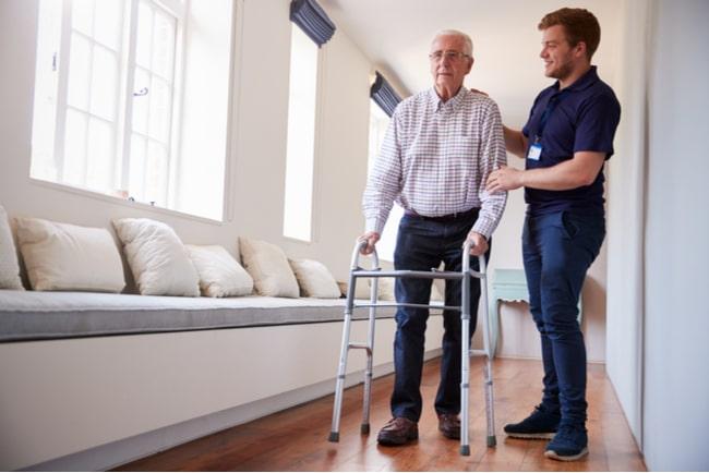 äldre man får hjälp av vårdare att gå med gåbord