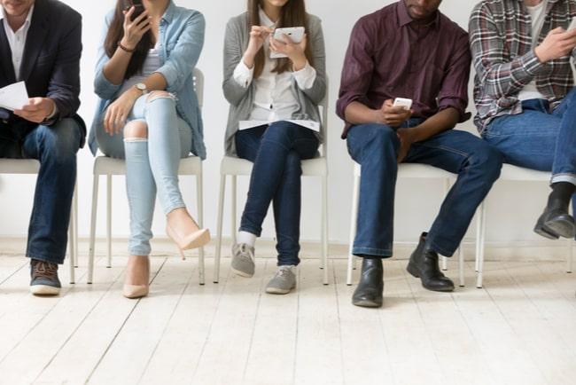 kvinnor och män sitter och väntar på arbetsintervju