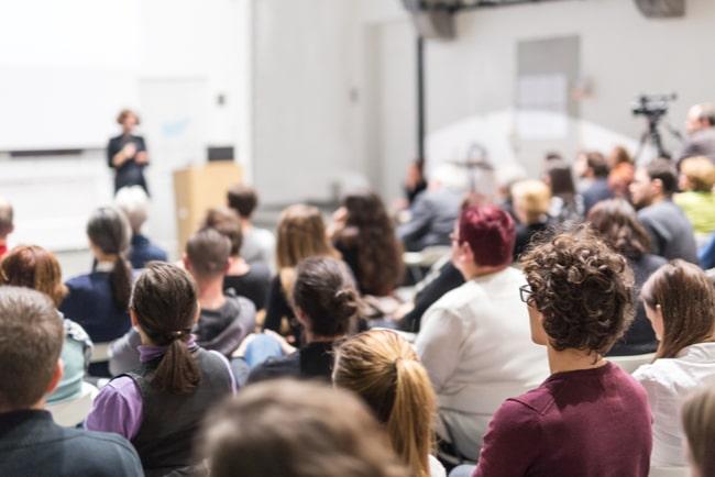 universitetsstudenter sitter i föreläsningssal och lyssnar på en lärare