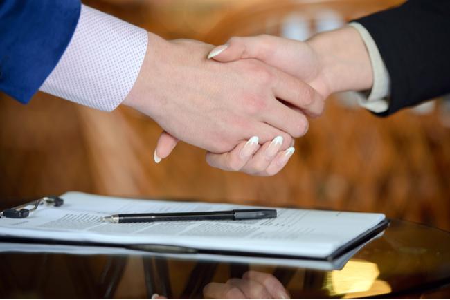 två händer skakar hand över ett påskrivet avtal