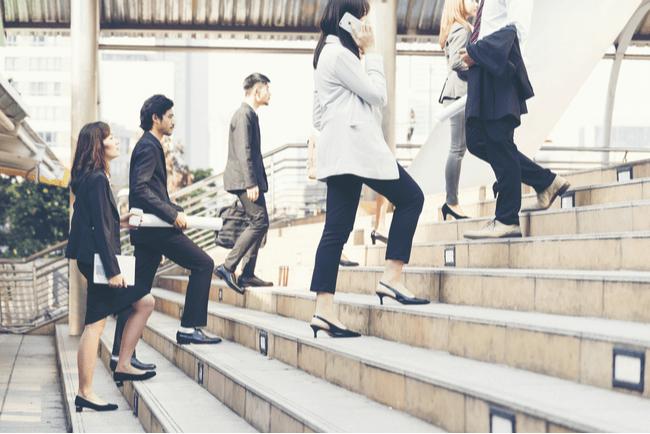 affärsklädda personer går uppför en trappa
