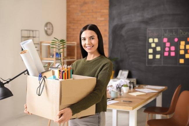 glad kvinna går från kontor med saker packade i en låda