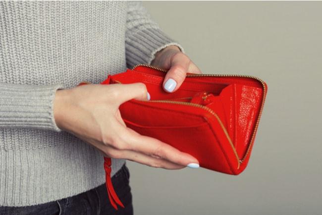 närbild på händer som håller i tom röd plånbok