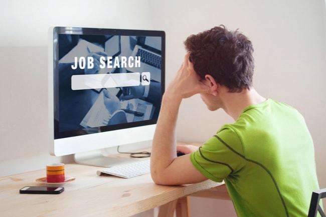 ung man söker jobb framför dator vid skrivbord