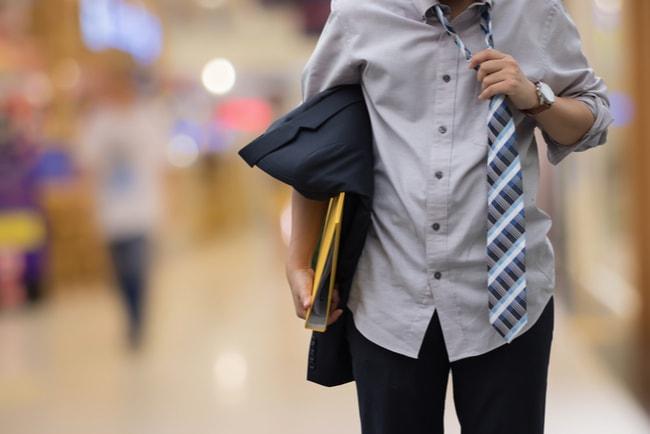 närbild på man med slips och pärm under armen