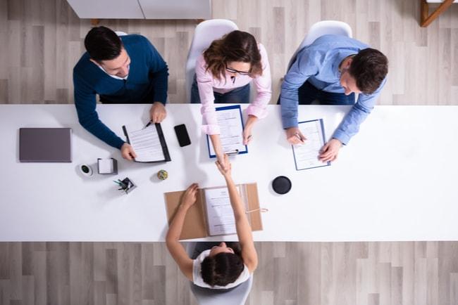 tre rekryterare skakar hand med ny medarbetare efter jobbintervju