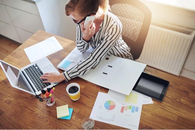 kvinna jobbar från hemmakontor med dator och telefon