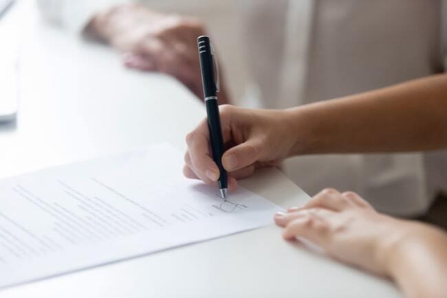 Händer på en person som håller i en penna och skriver under ett avtal.