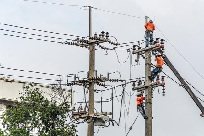 Tre män i arbetskläder som har klättrat upp i en elstolpe.