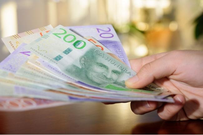 hand håller i svenska sedlar