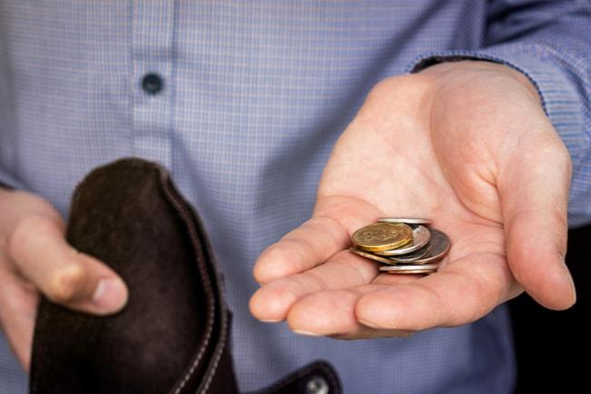 man håller tom plånbok och ett par mynt