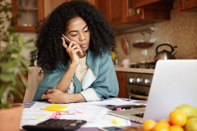 Nedstämd kvinna sitter vid köksbordet med laptop och talar i telefon.