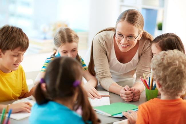Kvinnlig pedagog samtalar med barn i grupp.