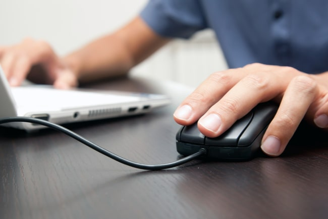 En manlig hand håller i en mus till en pc.