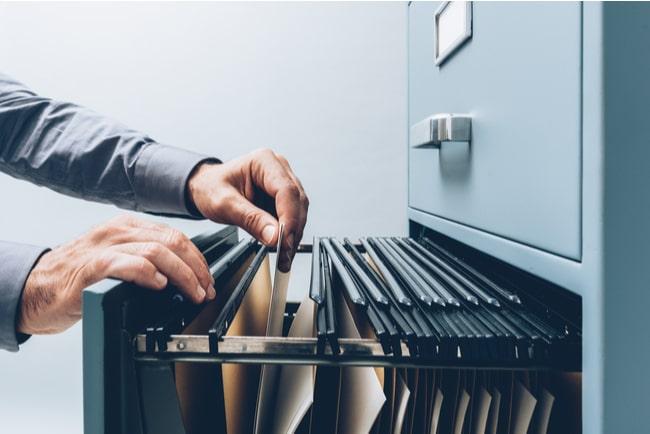 man tar ut mapp från arkivskåp