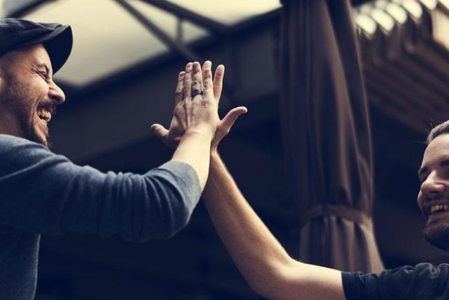 Två män som gör en high five med varandra.
