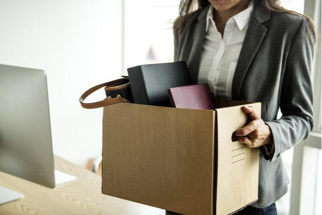 Kvinna bär en kartong med sina tillhörigheter som hon haft på sitt arbete.