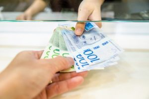 kvinnlig hand räcker över svenska sedlar i olika valörer till en manlig hand.
