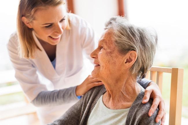 Kvinnlig hemsjukvårdare tar hand om en äldre kvinna på hembesök.