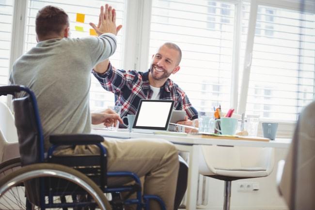 En man i rullstol vid skrivbord gör high five med en annan man som sitter bredvid.