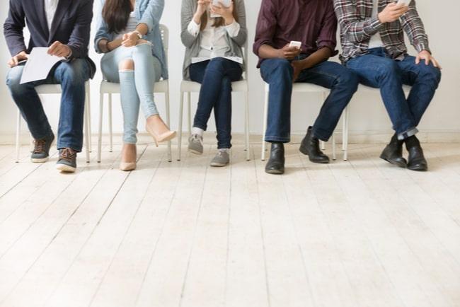 Fem olika människor som sitter och väntar på att få komma in på en intervju.