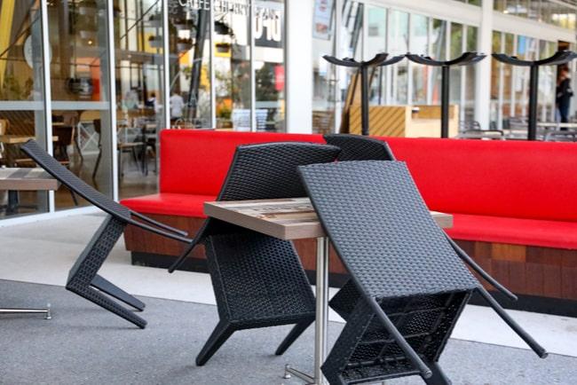 Bord och stolar på en uteservering som står uppställda och visar att restaurangen har stängt.