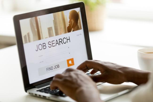 Dator med texten Job Search och händer som söker.